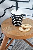 Kekse und gepunktete Tasse auf einem Holzhocker