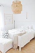 Basketwork lampshade above bed in bedroom decorated entirely in white