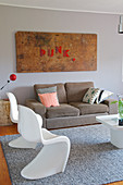 Classic white chairs and sofa on grey rug below old wooden door with motto in red lettering mounted on wall