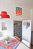 Colourful tablecloth on table, red pendant lamp and vintage adverts above open pantry door