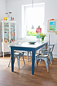 Old blue dining table and metal chairs next to window