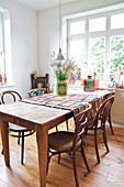Bistro chairs around wooden table and collection of retro accessories in dining room