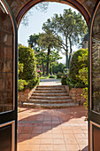 View through arched doorway across terrace and up steps into garden