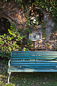 Green park bench against climber-covered stone wall
