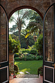 View through arched doorway of palm trees in exotic garden