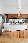 Open kitchen with island, cupboard fronts partly made from recycled wood