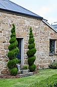 In Spiralform geschnittene Hecken am Eingang eines Natursteinhauses