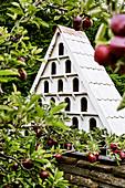 Large bird house on the garden wall near the apple trees