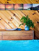 Kommode vor Holzwand mit Bildersammlung im Schlafzimmer, im Vordergrund türkisfarbene Bettwäsche