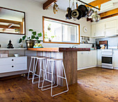 Wooden breakfast bar with filigree bar stools in an open kitchen