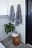 Handtücher, Zimmerpflanze und Baumstamm-Hocker im Badezimmer mit weißen Wandfliesen
