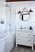Vanity unit next to bathtub with shower screen in white tiled bathroom