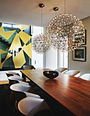 Large, airy, spherical lamps above long wooden table in dining room