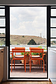 Orange chairs around table on balcony below cloudy sky