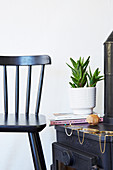 Black spoke-back chair next to stove with modern jewellery on top