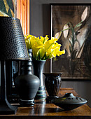 Black lamp and black vase of yellow calla lilies