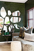 Wooden side tables and scatter cushions on sofa below mirrors on wall with crocodile-effect wallpaper