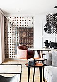 View past side table into dining area with designer leather armchair and mirrored door