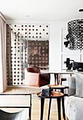 Blick über Beistelltische auf Essbereich mit Designer-Lederstuhl und Spiegeltür