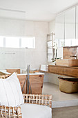 Designer chair, wood-clad bathtub and washstand in bright bathroom