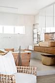 Designerstuhl, Badewanne mit Holzverkleidung und Waschtisch in hellem Badezimmer