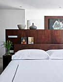 Bed with dark wooden partition headboard in bedroom