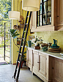 Ladder in front of glass-fronted wall units in country-house kitchen