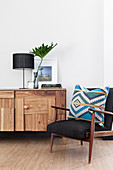Table lamp and large leaf in vase on top of sideboard with patchwork wooden front next to patterned cushion on armchair