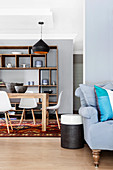 Colourful scatter cushions on grey sofa and side table in front of dining area with classic chairs and crockery on open shelves