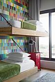Etagenbetten mit Aufhängung an der Wand mit bunter Tapete