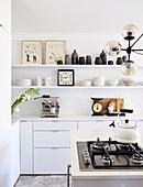 Regale und Kochinsel mit Gasherd in weißer Küche