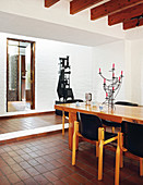 Old designer chairs at wooden table on terracotta-tiled floor