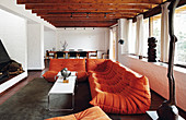 Orange designer sofa in living room with wooden ceiling beams