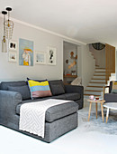 Grey sofa in modern living room with foot of staircase in background