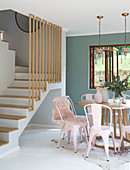 Round dining table and pink metal chairs at foot of staircase