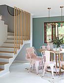 Runder Esstisch mit rosafarbenen Metallstühlen vor der Treppe