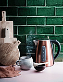 Kettle and a steaming cup in front of green tiles