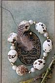 Circlet of threaded quail eggs and beads on old book