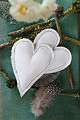 Two fabric hearts and spotted feather on twigs
