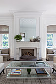 Glass coffee table and brown ottoman in front of white fireplace with mirror