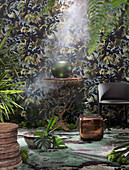 Round side table, armchair and cube table against wallpaper with plant pattern