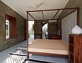 Four-poster bed and other wooden fittings in modern, concrete architect-designed house