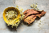 Dried elder and chamomile flowers in papier mâché bowl and dried rhubarb leaf
