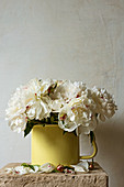Bouquet of white peonies in yellow enamel jug on stone slab
