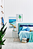 Bedroom with accessories in aqua tones and white wooden paneling