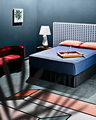 Double bed with individual headboard, blue blanket and pillows