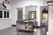 Mobile stainless steel island, white sideboard and French wall mirror in the kitchen