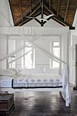 Double bed with white canopy in the bedroom