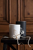 Black and white candle lanterns with leaf motifs and string bow