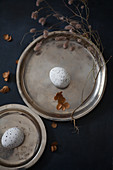Dried flowers around speckled eggs on two pewter plates